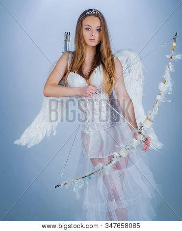 Cute Little Female Cupid Shoots A Bow. Angel Children Girl With White Wings. Innocent Girl With Ange