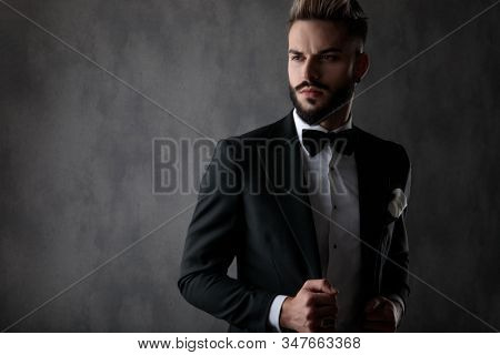 sexy businessman wearing black tuxedo standing and fixing his jacket while looking  away with a dramatic look on his face on gray studio background
