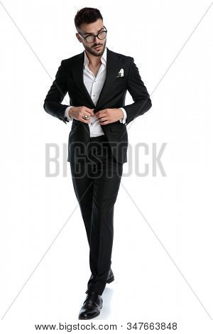 fine formal business man wearing black tuxedo and eyeglasses walking and fixing jacket while looking aside cautious against white studio background