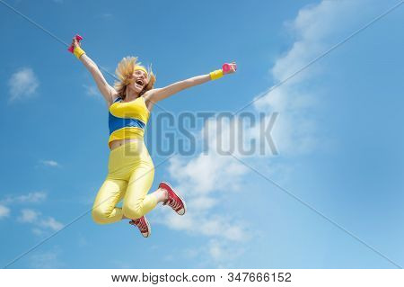 Young Sporty Excited Girl Jumping Happily With Hands Up On Sky Background Outdoor, Panorama, Copy Sp