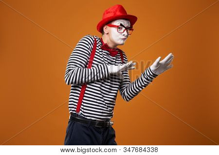 Sad mime in red hat and vest on orange background