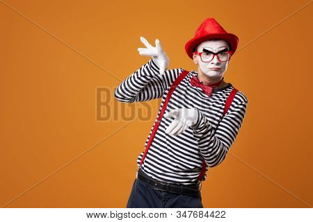 Mime in vest and red hat on orange background