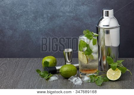 Set of bar tools: cocktail shaker, muddler, jigger, cocktail with ice in highball glass,  lime and mint on dark gray background with copy space. Bartender's tool. Mojito cocktail making.