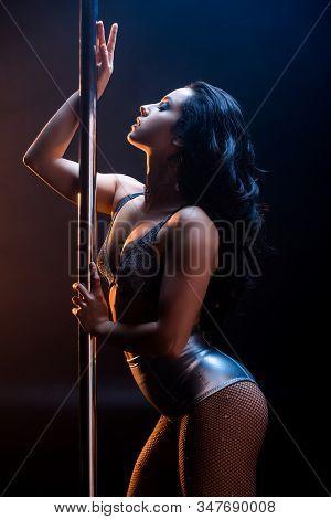 Side View Of Attractive Stripper In Underwear Dancing Striptease Near Pylon On Blue
