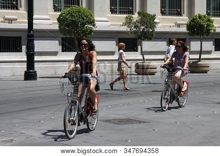 Seville, Spain - July 14, 2011:unknown Girls On A Bike Ride In The Center Of Seville
