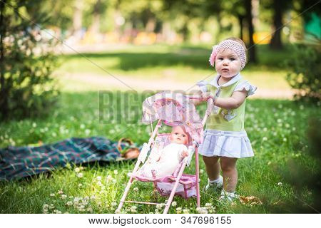 Small Baby Girl Walking On Grass And Rolling Toy Stroller With Doll