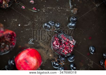 Rotten Pomegranates And Grapes In The Puddle. Spoilt Products.