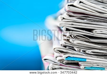 Newspapers Folded And Stacked On The Table  With Blue Background.closeup Newspaper And Selective Foc