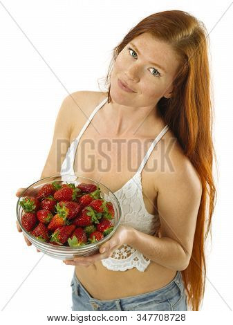 Photo Of A Gorgeous Young Woman With Long Red Hair Holding A Bowl Of Strawberries Over White Backgro