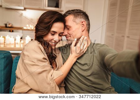 Image of happy caucasian couple taking selfie photo while having romantic candlelight dinner at home
