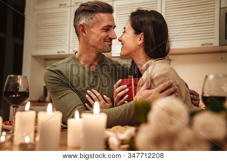 Image of happy adult man giving present box to his girlfriend during romantic candlelight dinner at home