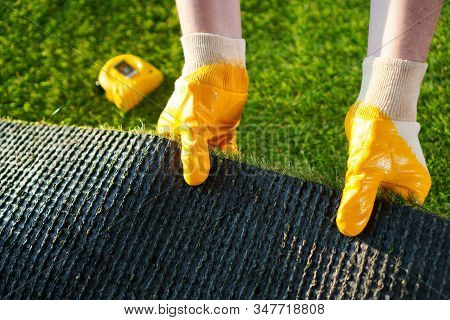 Greenering With The Green Artificial Grass Background. Worker Holds A Roll Of Green Artificial Turf.