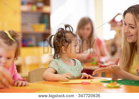 Worker With Babies In Creche. Kids Group On Lesson In Kindergarten