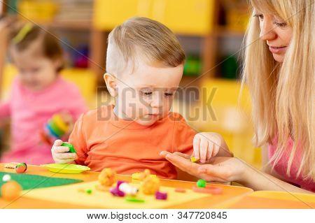 Teacher With Babies In Creche. Kids Play Clay In Kindergarten
