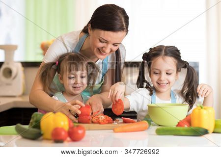 Happy Mother And Her Kids Cooking And Cutting Vegetables On Kitchen