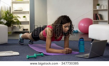 Mixed Race Young Woman Doing Online Workout In Front Of Laptop, Exercising