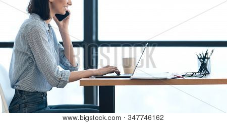 Unrecognizable Girl Talking On Mobile Phone And Using Laptop Computer In Modern Office, Side View, P