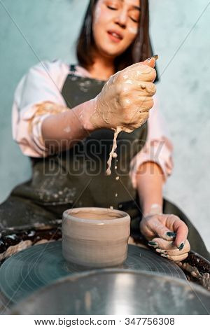 Woman Pouring Water On Pottery Wheel With Clay In Ceramist Workshop. Creating Handmade Dishware