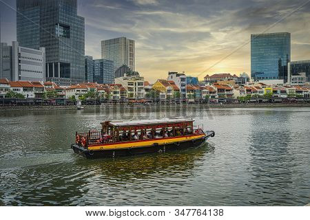 Singapore. January 2020.  A Boat On The Singapore River With Typical Shop Houses In The Background