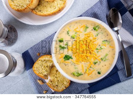 Top View Of A Bowl Of Creamy Broccoli Cheddar Cheese Soup With Toasted Cheese Bread