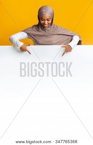 Free Space For Your Ad. Black Muslim Woman In Headscarf Looking Down And Pointing At Blank White Adv