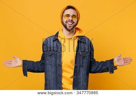 Smirked Young Hipster Guy In Fashion Jeans Denim Clothes Posing Isolated On Yellow Orange Background