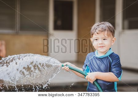 Cute Young Boy Playing Outside With Water In Nature