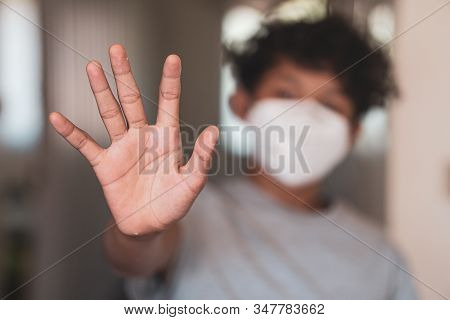 Young Asian Boy Raising His Hand And Wearing A Protective Mask, Fear Over Stopping Flu And Coronavir