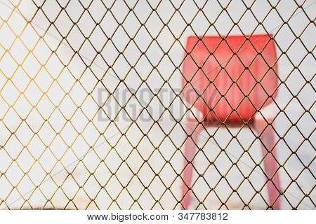 Metal Security Fence With A Red Chair Behind