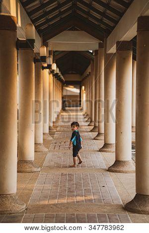 Cute Young Mixed Race Boy Walking Along Path Woth Columns