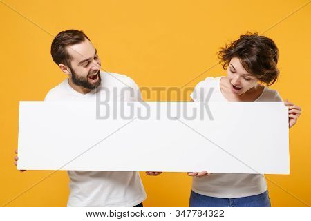 Curious Young Couple Friends Bearded Guy Girl In White T-shirts Isolated On Yellow Orange Background