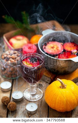 Christmas Red Wine Mulled Wine With Spices And Fruits On A Wooden Rustic Table. Traditional Hot Drin