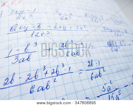 Math Formulas Are Written In A Notebook With A Pen. The Solution Of Examples And Problems In A Noteb
