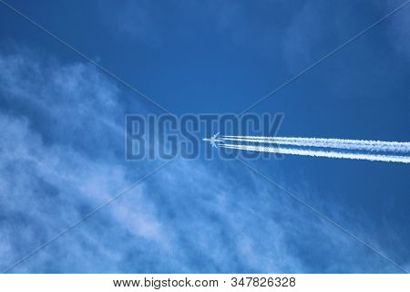 Airplane Contrail Created From A Moist Upper Level Atmosphere Surrounded By Cirrus Clouds Taken From