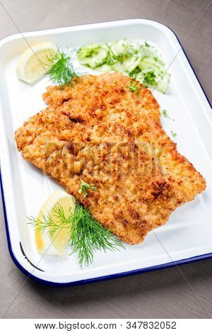 Traditional deep fried Wiener schnitzel from veal topside with cucumber salad and cranberry jam offered as closeup on a white tray