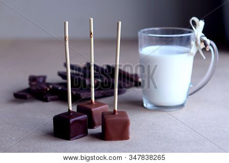 Chocolate Cubes On A Stick With Milk Cup And Aromatic Cocoa And Chocolate On Brown Background. Hot C