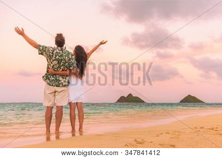 Happy beach vacation couple tourists enjoying sunset with arms up in freedom view from behind. Woman and man standing in hawaiian shirt against ocean background dusk in Lanikai, Oahu, Hawaii.