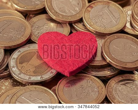 Close-up Image Of One And Two Euro Coins With Red Heart Showing Passion For Money