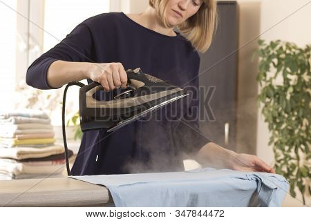 Woman Is Standing At An Ironing Board And Holding An Iron From Which Steam Escapes. Woman During Hou
