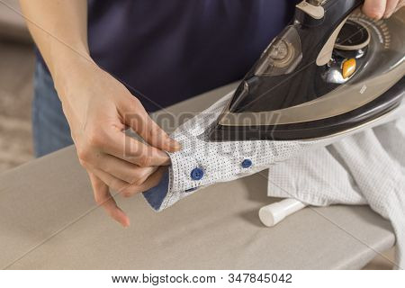 Female Hands Iron The Shirt Sleeve On A Stand On An Ironing Board. Ironed Clothes Lie On The Table I