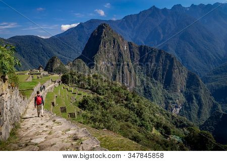 Man Walking The Inca Trail, The Huayna Picchu Mountains Behind. Unesco World Heritage. Peru, South A