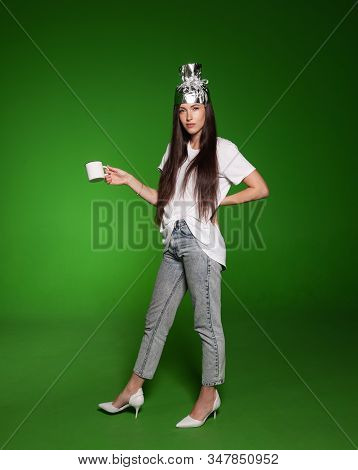 Attractive Young Woman Wearing Tinfoil Hat For Protection. Conspiracy Theory Concept. Woman Holding