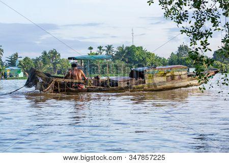 MEKONG DELTA, VIETNAM - CIRCA NOVEMBER 2019: Vietnamese farmers haul goods by boats circa November 2019 in delta of Mekong. Mekong delta is a popular tourists destination.