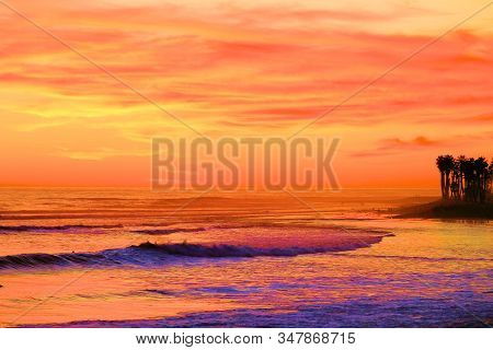 Waves Crashing Onshore With Palm Trees In The Distance During A Dramatic Sunset While High Level Cir