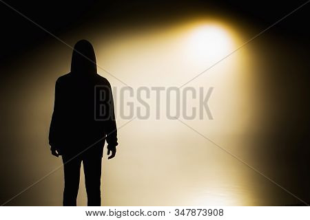 Silhouette Of A Man In The Darkness. Night Photography. Shadow In Mist. Mysterious Anonymous Figure