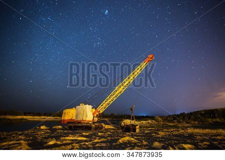 Night Photography Outdoor. Bulldozer On Background Of Starry Sky. Long Exposure. Stars In Night Blue