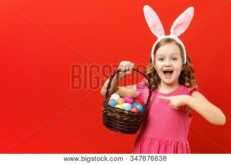 Enthusiastic Child In The Ears Of A Bunny On A Red Background. Little Girl Shows A Finger On A Baske