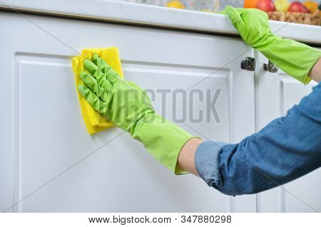 Woman In Gloves With Rag Washing, Cleaning, Polishing Furniture Doors On Kitchen, Cleaning House