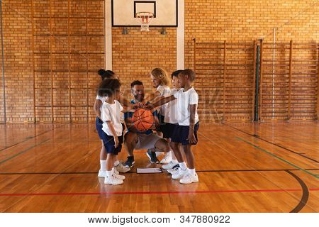 Happy schoolkids and basketball coach forming hand stack at basketball court in school