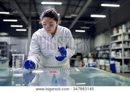 Laboratory brunette girl with flask with blue liquid in her hands checks quality